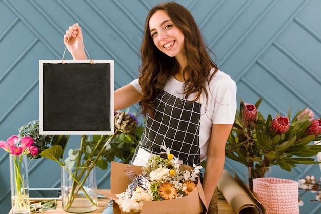 Tiro médio feliz florista segurando uma placa preta Foto gratuita