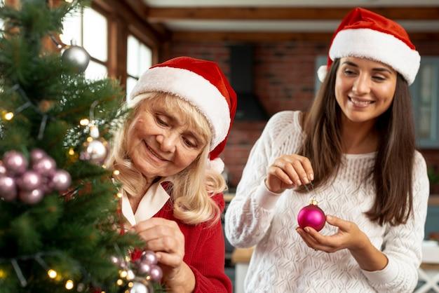 Tiro médio feliz mãe e filha decorando a árvore de natal Foto gratuita
