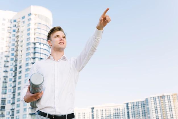Tiro médio, homem apontando, algo Foto gratuita