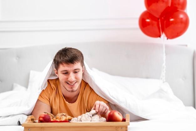 Tiro médio homem com café da manhã na cama Foto gratuita