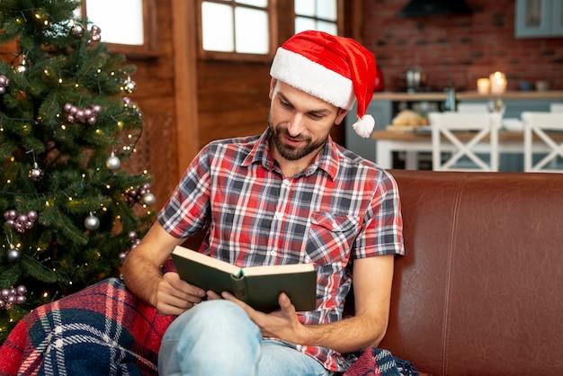 Tiro médio homem com chapéu vermelho, lendo um livro Foto gratuita