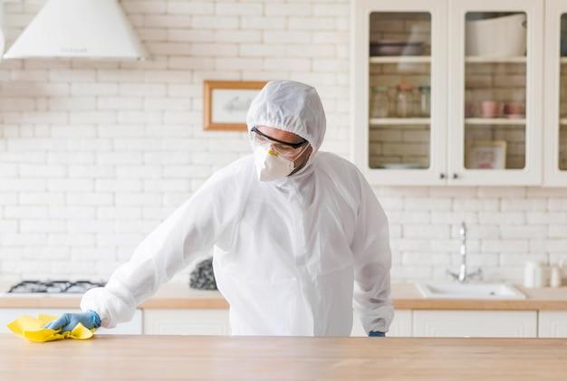 Tiro médio homem limpando a mesa de madeira Foto Premium