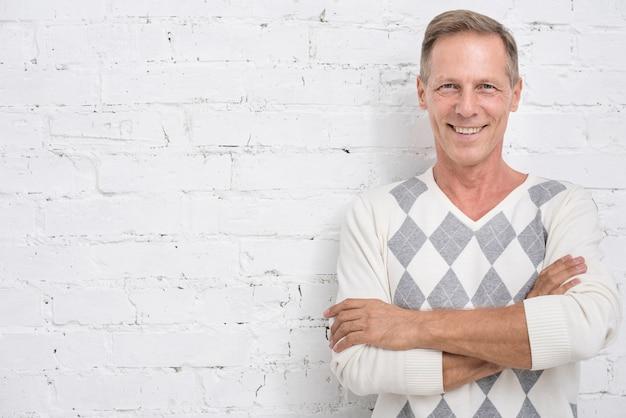 Tiro médio homem sorridente com fundo de tijolo Foto Premium