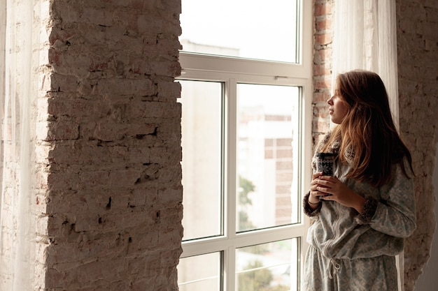 Tiro médio menina bonita olhando pela janela Foto gratuita