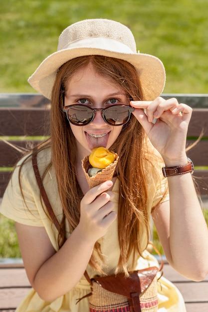 Tiro médio, menina, comer sorvete Foto gratuita
