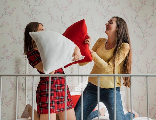 Tiro médio meninas felizes em uma luta de almofadas Foto gratuita