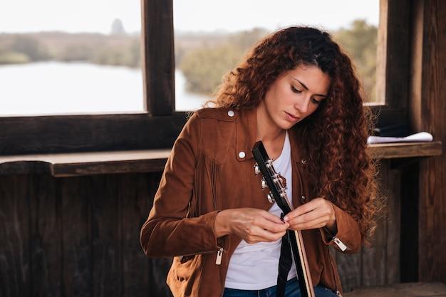 Tiro médio, mulher, afixando, um, guitarra Foto gratuita