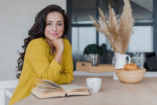 Tiro médio mulher bonita com livro e copo Foto gratuita
