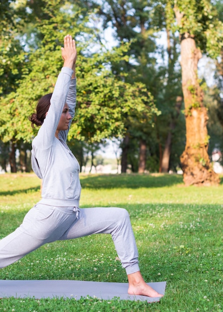 Tiro médio, mulher, esticar, ao ar livre Foto gratuita