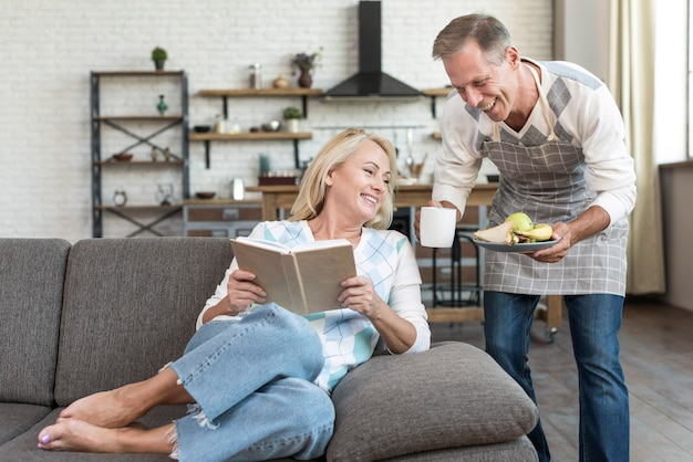 Tiro médio mulher feliz lendo no sofá Foto gratuita