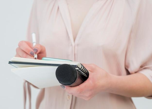 Tiro médio, mulher segura, microfone, e, escrever notas Foto gratuita