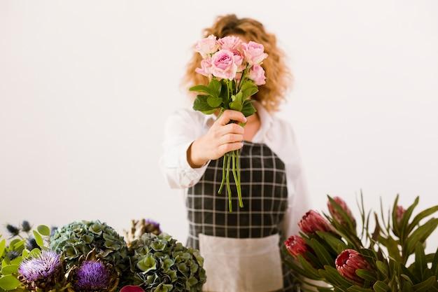 Tiro médio mulher segurando um buquê de rosas Foto gratuita