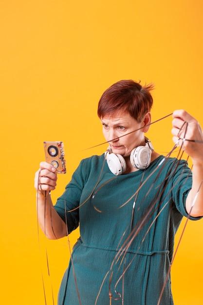 Tiro médio, mulher sênior, tocando, com, fita cassete Foto gratuita