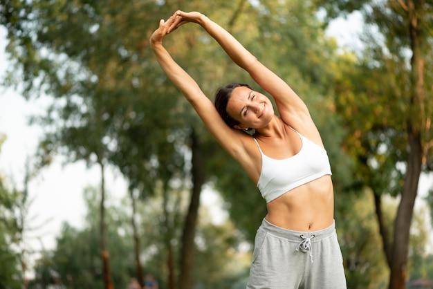 Tiro médio mulher sorridente, esticando o corpo Foto gratuita