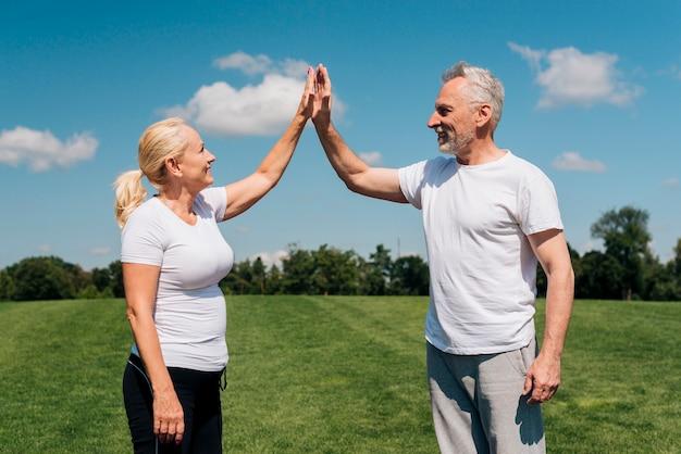 Tiro médio, pessoas velhas, fiving alto Foto gratuita