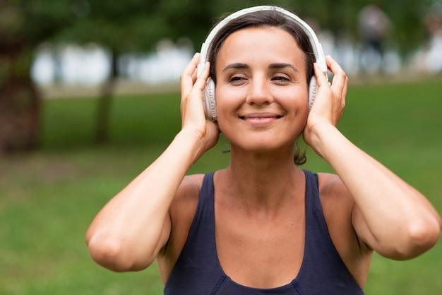 Tiro médio sorridente mulher com fones de ouvido Foto gratuita