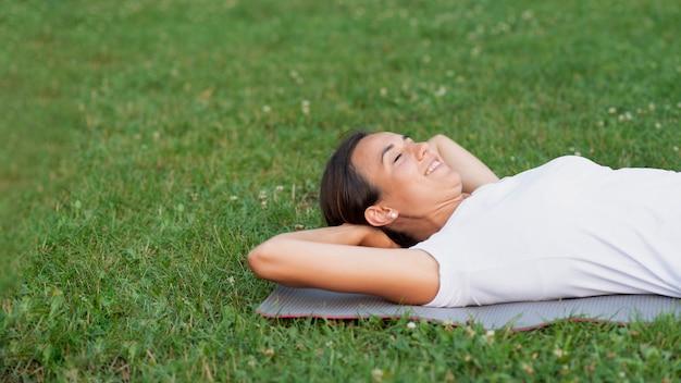 Tiro médio sorridente mulher deitada na grama Foto gratuita