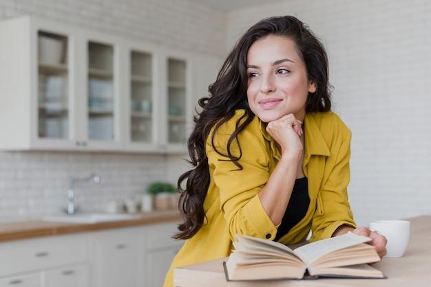 Tiro médio sorridente mulher lendo na cozinha Foto gratuita
