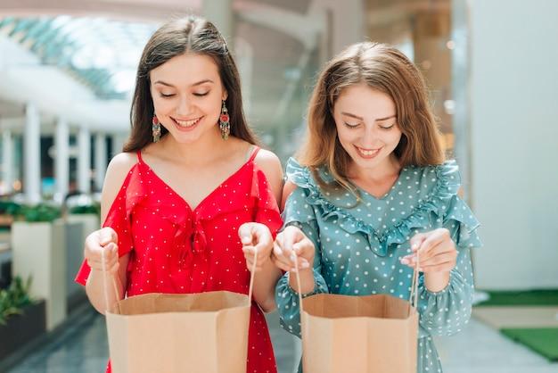 Tiro médio, sorrindo, meninas, olhar, dentro, sacolas Foto gratuita