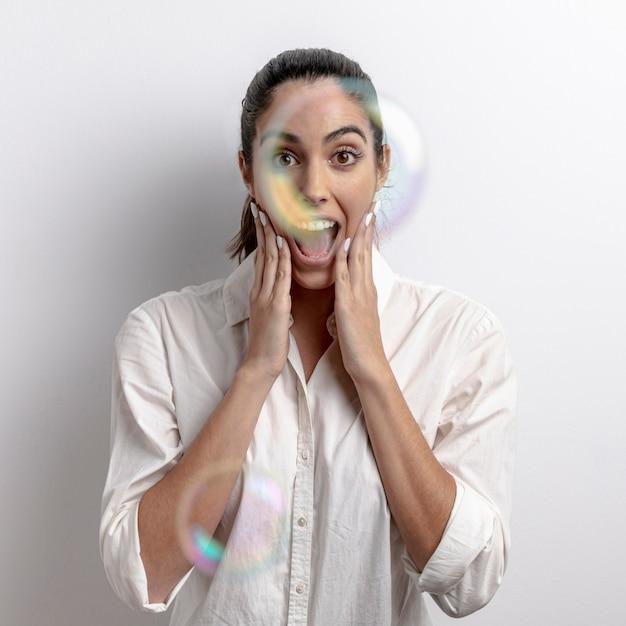 Tiro médio surpreendeu a mulher com balões de sabão Foto gratuita