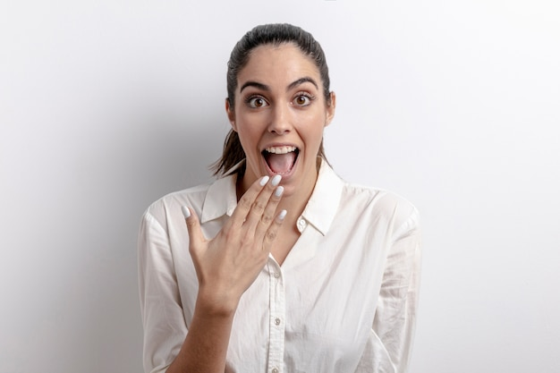 Tiro médio surpreendeu a mulher com fundo branco Foto gratuita
