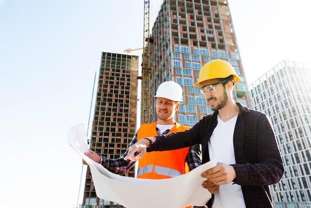 Tiro médio, vista baixa ângulo, de, engenheiro, e, arquiteta, supervisionando, construção Foto gratuita