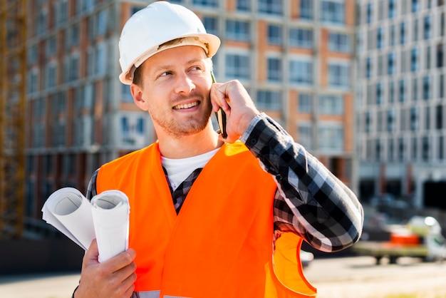 Tiro médio, vista lateral, de, engenheiro, conversa telefone Foto gratuita