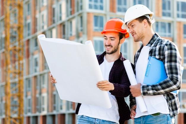 Tiro médio, vista lateral, de, engenheiro, e, arquiteta, supervisionando, construção Foto gratuita