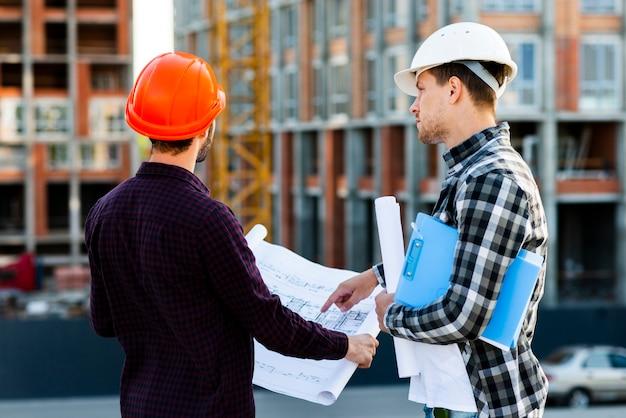 Tiro médio, vista traseira, de, engenheiro, e, arquiteta, supervisionando, construção Foto gratuita