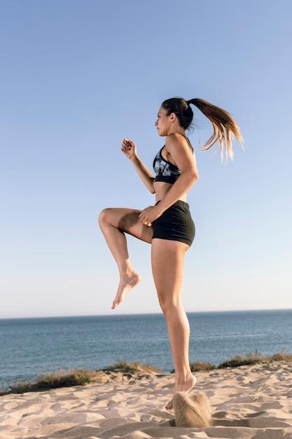 Tiro, mulher, em, sportswear, sacudindo, praia Foto gratuita