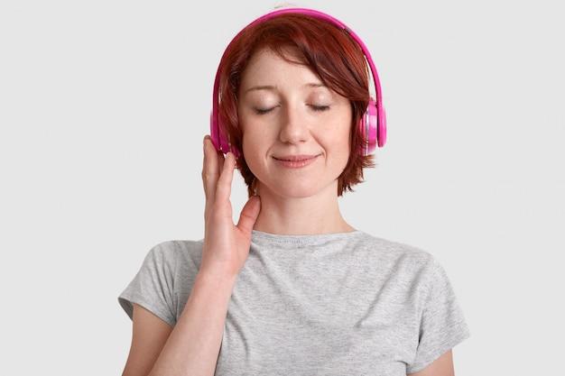 Tiro na cabeça da jovem satisfeito usa fones de ouvido, ouve música favorita, fecha os olhos de prazer, goza de som alto, vestido com camiseta casual, isolada sobre parede branca. conceito de passatempo Foto gratuita