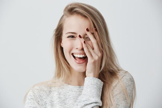 Tiro na cabeça de mulher bonita com olhos escuros, cabelos longos loiros, sorriso gentil feliz, regozijando-se com seu sucesso. Foto gratuita