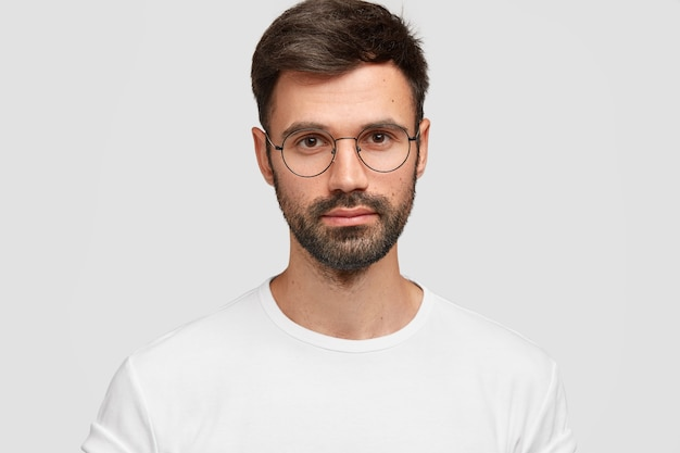 Tiro na cabeça de um freelancer masculino bonito com aparência atraente, tem barba e bigode escuros, parece diretamente com uma aparência séria, usa roupas casuais brancas. monocromático. expressões faciais. Foto gratuita