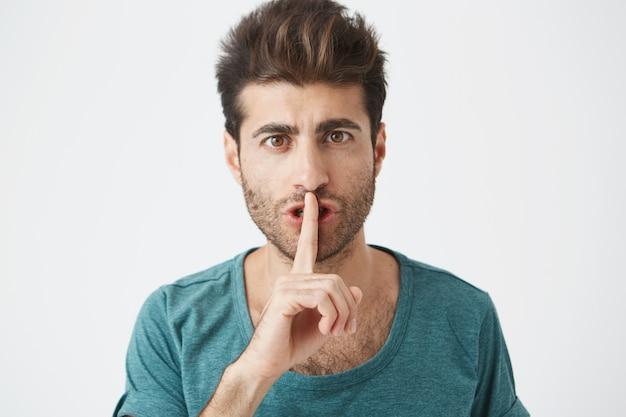 Tiro na cabeça do homem caucasiano elegante elegante casual camiseta azul, segurando o dedo indicador nos lábios, pedindo para manter o silêncio na biblioteca. Foto gratuita