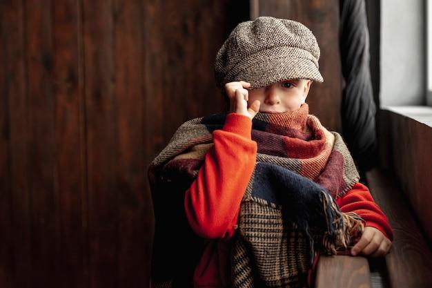 Tiro na moda menino moderno com chapéu e cachecol Foto gratuita