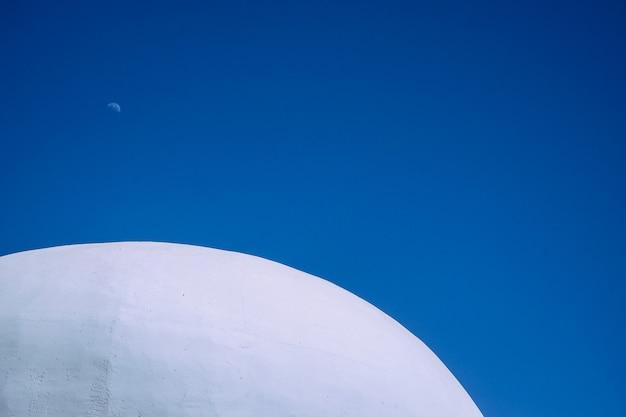 Tiro próximo da parte superior do prédio redondo de concreto branco com céu azul claro ao fundo Foto gratuita