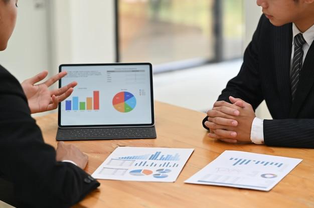 Tiro recortado consulta com tablet digital e planejamento de marketing. Foto Premium