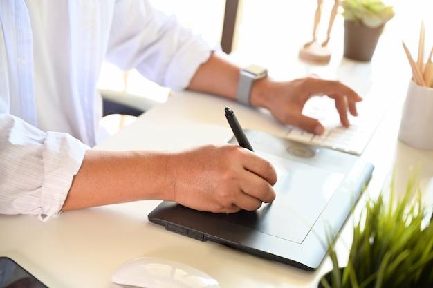 Tiro recortado de designer trabalhando com tablet de desenho digital de desenho para design criativo no escritório Foto Premium