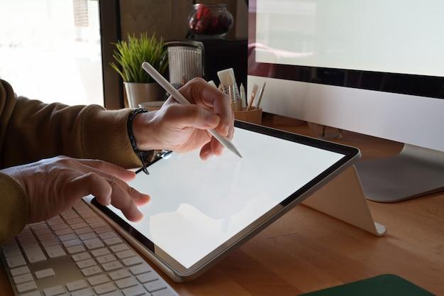 Tiro recortado de designer usando a mesa digitalizadora enquanto estiver trabalhando com o computador no estúdio ou no escritório Foto Premium