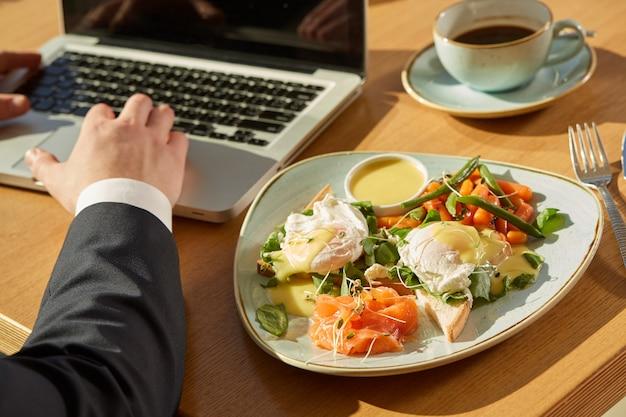 Tiro recortado de um empresário trabalhando no laptop durante café da manhã no café Foto Premium