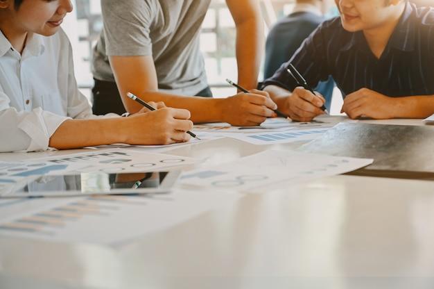 Tiro recortado inicie o negócio com o jovem empresário consultar reunião na mesa de trabalho. Foto Premium