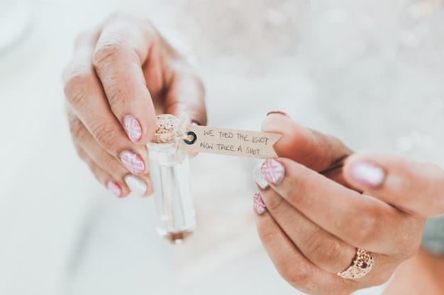 Tiro seletivo closeup de uma mulher segurando uma pequena garrafa de vidro com palavras escritas em uma etiqueta Foto gratuita
