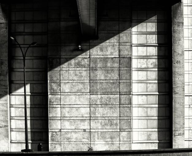 Tiro simétrico em escala de cinza de uma parede sombreada de pedra - depressão, conceito de solidão Foto gratuita