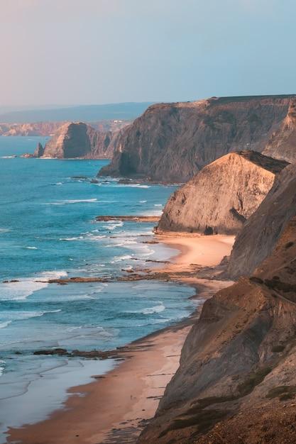Tiro vertical das belas falésias rochosas à beira-mar sob o incrível céu azul claro Foto gratuita