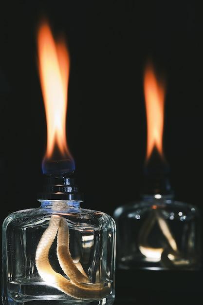 Tiro vertical das chamas dos difusores de perfume no escuro Foto gratuita