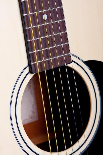 Tiro vertical das cordas de uma guitarra branca durante o dia Foto gratuita