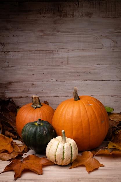 Tiro vertical de abóboras, rodeado de folhas com um fundo de madeira para o halloween Foto gratuita