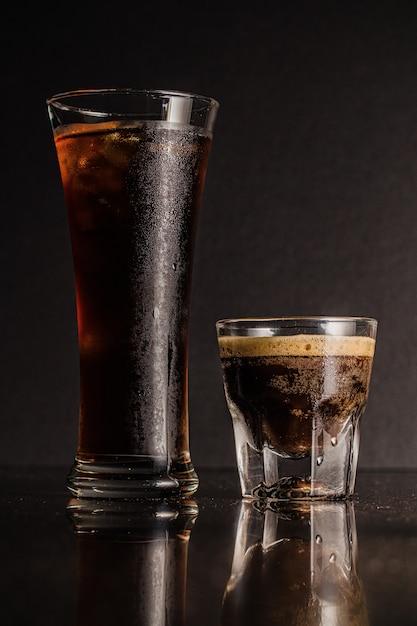 Tiro vertical de copos de licor e café com reflexões Foto gratuita