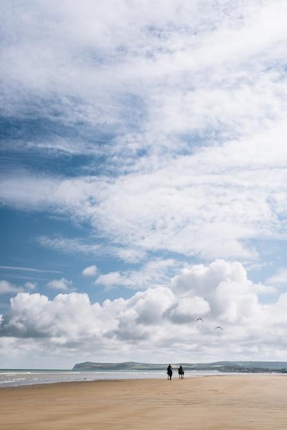 Tiro vertical de duas pessoas andando a cavalo ao longo da praia sob um céu nublado na frança Foto gratuita