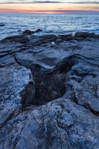 Tiro vertical de formações rochosas no mar adriático em savudrija, ístria, croácia Foto gratuita
